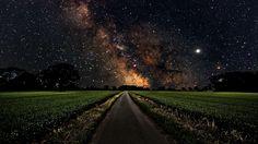 Milky Way over a green field wallpaper