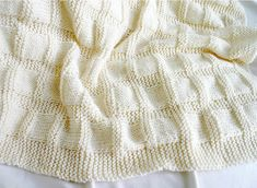 Cream Knit Baby Blanket- looks like a very easy pattern to copy, using garter stitch as border and stockinette stick to create the flat squares.