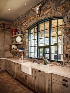 Mountain style kitchen photo in Houston with a farmhouse sink and recessed-panel cabinets