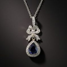 Delicately hand fabricated in platinum during the first or second decade of the twentieth century, this exquisite Edwardian era drop features a pear shape sapphire weighing approximately 1.50 carats. The radiant royal blue gemstone in elegantly framed with tiny round diamonds surmounted by a sparkling bow. As sweet as can be. 1 inch; the new platinum chain measures 16 inches. Accompanied by gemological report from Stone Group Laboratory stating: Indications of Thermal Enhancement, Ceylon…