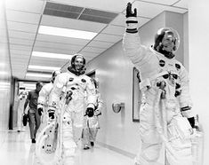 Apollo 11 Commander Neil A. Armstrong, waving, walks in a hallway of the Manned Spacecraft Operations Building with Command Module Pilot Michael Collins and Lunar Module Pilot Edwin E. Aldrin, Jr. The three are on their way to the launch complex on launch day. July16, 1969.