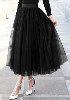 Front view of model in tulle midi skirt and black top