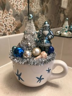 Vintage blue Santa in starfish cup with a few shells front and back