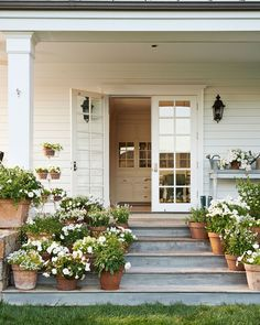"Natural light also floods in through the French doors along the wraparound porch, and ""everywhere you go, you can see the garden,"" Blazona says. In this photo: White flowers—including salvia, violas, petunias, begonias, and lantana—adorn the side porch."