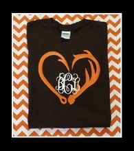 Photo shows a chocolate brown monogram tee with orange and white front only design.