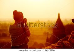 female traveler photographing temples at Bagan Myanmar Asia at sunrise by Warren Goldswain, via Shutterstock