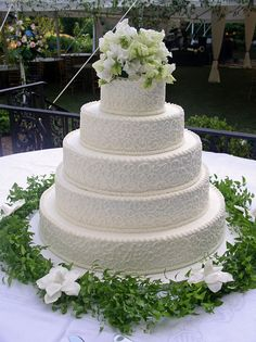 dense scrolls decorate the sides of this traditional wedding cake wwwcakesbygrahamcom more