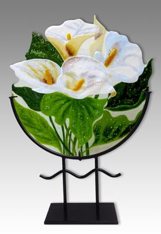 White Calla Lilies by Anne Nye. There is something so graceful and elegant about white flowers epitomized by white calla lilies. Nye has put together a bouquet of white callas in *kiln-formed:kiln-forming* glass, set them off with lovely green leaves and placed them in a custom made welded steel stand. Colors are perfect with any decor, will not fade and is easily cleaned with any glass cleaner.