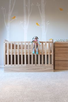 This modern crib is softened by the exposed wood grain and the addition of birch tree decals with cute birds.