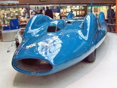 442 Bluebird. (1961)  Donald Campbell set a new World Land Speed Record of 403,10 mph (648.783 kph) in this car on the 17th July 1964  Bluebird cost £ 1 million to build and was powered by a Bristol-Siddeley Proteus 4,100 bhp gas turbine engine. The tail fin was a later addition, following a crash at Bonneville, Utah in 1960.  Lake Eyre, South Australia was then chosen because it was a desolate,flat, salt plain. However rain became one of a series of delays that dragged the record attempt on