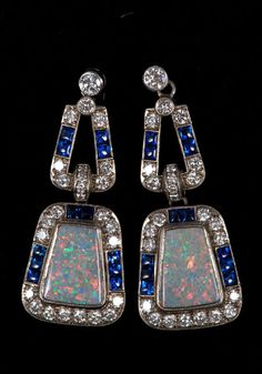 Pair Art Deco-style opal, diamond and blue sapphire pendant earrings with an opal surrounded by brilliant cut diamonds and calibre cut blue sapphires suspended from a diamond and sapphire loop in white gold (18ct) setting