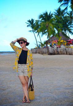 blazer amarelo largo com estampa de coqueiros preto e branco, maiô preto, chinelo e short listrado azul marinho e branco