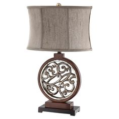Table lamp with a circular openwork base and oval shade.      Product: Table lampConstruction Material: Fabric,...