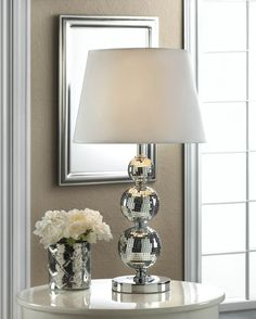 This dazzling table lamp will sparkle and shine, day or night! The circular base features three varied mirrored balls that reach up to hold a white fabric shade. This lighting accent will add glitz an