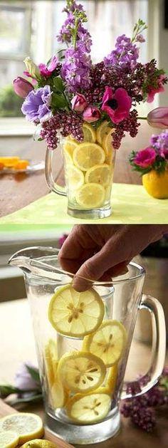 Ställ ner en smalare vas i kannan och dekorera utrymmet emellan med citron, lime,apelsiner mm