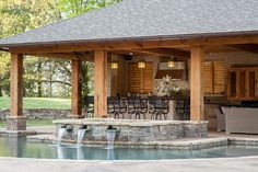 Outdoor dining area, seating area, and raised spa and water feature complete this backyard design.  Outdoor Solutions Brandon, MS