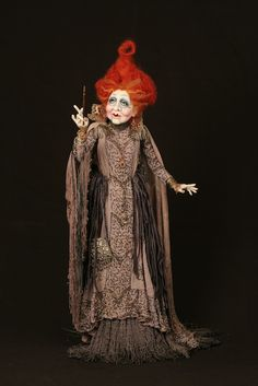 Mertel, by Dustin Poche'  The old Sorceress is trying to remember where she put her spell book. She is wearing the most haunting outfit in antique beaded slate gray silk, an aged gold collar and antique laces with fire cracker red hair.  34 INCHES (86.36 CM) TALL  Paper clay, acrylic paint, chalk powder, wire, wool crepe, antique beaded silk, velvet, linen, antique metal find, hand knitted lace.