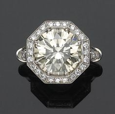 A diamond and platinum solitaire ring centering an old European-cut diamond, within an octagonal-shaped round brilliant-cut diamond surround and shoulders, completed by carved gallery; estimated central diamond weight: 6.25 carats.