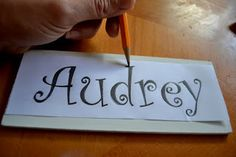 Print words or name on paper; turn over and cover the word with the side of a pencil; place pencil side on wood and secure with tape; use pencil to outline printed word -  this makes a template for you to paint.