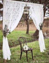 lace linen tied to wooden arbor to look like curtains for a vintage country wedding
