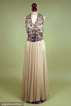MADELEINE VIONNET EVENING GOWN, LATE 1930s  Cream chiffon, sweeping full skirt, halter mobius band neck, bodice & wide belt hand embroidered in silver gilt, salmon silk floss, red paste jewels mounted on brass or silver