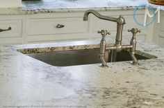 The island faucet sports an industrial design that compliments the veining in this Bianco Romano countertop.