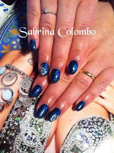 Unghie in gel monocolore blu stellato con nail art rosa stilizzata
