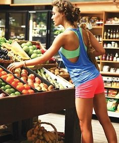 love this workout outfit and hairstyle. I also like that she's shopping for fruit just to make things even healthier