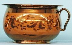 pottery & porcelain, England, An unusual brown banded copper lustre handled chamber pot, round having a simple round molded foot, rounded sides are surrounded by a wide brown band having copper lustre floral and scroll designs, sides tapered to a flared wide flattened collar, arched handle.