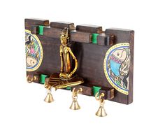 This key ring holder is made of mango wood. Artistically crafted with warli work. In betwwen the wooden panel is a figure in Dhokra work which enhances beauty of this keyhook stand. Further beautified by bells.  (There may be very MINOR VARIATIONS in color combinations and figure designs, between displayed and dispatched products, due to variety of artisans who handcraft the products. The look, feel and quality will , however, be consistent with what you see. That is an Indikala promise).
