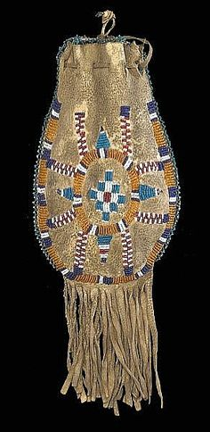 Partially beaded on one side to depict a stylized turtle, the reverse showing an abstract bird in flight, with bands of edge beading and fringe suspensions. length 12in