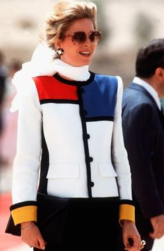 Vanity Fair's Best Dressed List: H.M. QUEEN NOOR OF JORDAN  Year Inducted: 1988  Style Hallmarks: Queen Noor was inducted for her stylish balance of the conservative, covered attire required of her position and the ever changing trends of the day. In a Mondrian-inspired skirt suit, she's shown here in 1984 awaiting the Jordanian arrival of Queen Elizabeth II.