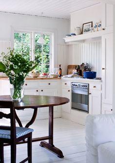 Platsbyggd inredning i köket, från danska Simonsen og Czechura. Kring det franska vinprovarbordet står värmländska allmogestolar.