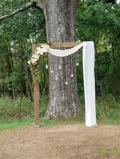 Light brown arbor with flowers and jars hanging from twine with fabric draped across one side