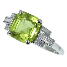 Art Deco platinum diamond ring with peridot 1920's Platinum, diamond and peridot ring with typical architectural Art Deco design. The central square emerald cut peridot is flanked left and right by three baguette cut diamonds.