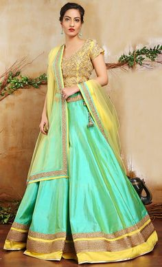 Sea Green Lehenga Choli This set features a yellow dabka and neem zari embellished blouse in gold. It is paired with a sea green lehenga is pure silk base with gold antique embellished border around the hem and waist. It comes along with a yellow net dupatta with gold antique border.