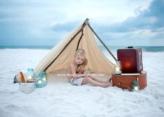 child under a tent on the beach. Such a great picture idea.
