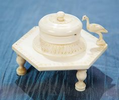 """VERY RARE FRENCH CARVED BONE WAX CASE 2 1/2"""" (6 cm.) w. Of carved bone in the shape of a garden table with center lidded jar for holding of wax,and decorative legs,carving and an exotic bird as detail. French,mid-19th century."""