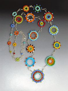 GLASS NECKLACE - CIRCUS COLLECTION  Handmade lampwork glass bead and sterling silver necklace featuring colorful glass disc beads.  This lovely necklace is composed of SRA artisan crafted lampwork playful disc shaped beads (made by me) in a variety of sizes with the largest measuring 40 mm diameter. The beads are wire wrapped with sterling silver wire and incorporated into sterling silver chain. This necklace is secured by a sterling silver lobster clasp. Every bead is made one at a time…