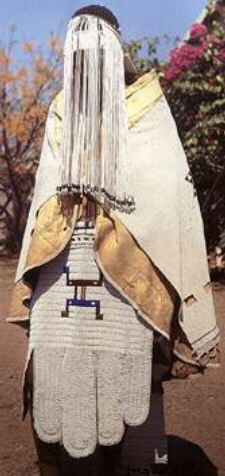 A Ndebele bride in intricate beadwork. The bridal veil (Isiyaya) is worn by the bride's attendant since the bride may not feed herself, drink, or do other activities. This is a very important role for the young girl, and the majestic regalia reflects this important position.
