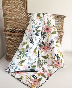 Our Wholecloth Quilts are perfect for the on the go, in your nursery, or on your toddlers bed. Designer high quality cotton fabrics and thread. Cozy batting is Warm Company Warm and White Needled Cotton brand. This Wholecloth Quilt is made with a contrasting blue and pink boho floral indie pattern designer fabric and eye popping black and white stripped binding. The quilting is done in a soft white & black thread using an improv crosshatch style so each one is unique. Quilt measures 40 x...
