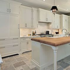 Lux white kitchen with wood countertop on island.