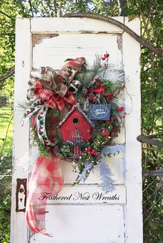 This Christmas Wreath is Made on a Grapevine Base. I have Layered the Wreath with an Assortment of Snowy and Frosted Pine, Red Berries, Faux Boxwood with Cream Berries and Sparkly Red Berry Twigs. I have added a Red Birdhouse with a Snowy Rooftop and Perched Two Cardinals within the Wreath. The Wreath is Finished out with a Large Checked Deco Mesh, Wired Christmas Plaid Ribbon, a Wired Cardinal Print Ribbon and a Linen Look Wired Christmas Ribbon. This Wreath Measures 25 in Length...this…