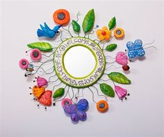 Create a wreath by covering cut out pizza rounds with papier mache. Form little flowers, leave, birds, or butterflies to add when completed.