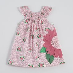 Smocked poplin dress features dimensional flower applique with interlock petals, ruffle center and button closure at back.