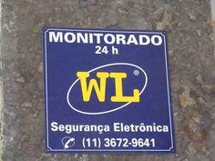 Placa da empresa WL de segurança eltrônica, informando que o referido local é monitorado 24h. Emissor: Empresa WL/ Destinatário: Usuários da loja na qual placa foi afixada, possíveis assaltantes/ Época: não é possível determinar, mas é provável que seja recente, pois não apresenta sinais de desgaste.
