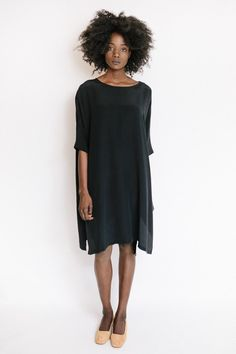 "The silk dress in black from Revisited Matters features a loose fitting silhouette with short sleeves and side slits. Also available in marsala. Model is 5'9"". - One size fits most - 100% Silk - Dry c"