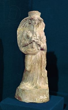 Statuette of a woman playing a double flute, from Tunisia (polychrome stone). Punic, (4th century BC) / Musee National de Carthage, Carthage, Tunisia / Giraudon / The Bridgeman Art Library