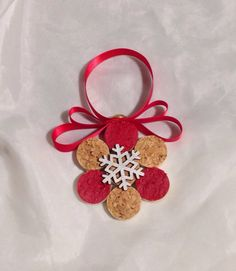 These adorable ornaments are made from slices of used wine corks put together and topped with a silver snowflake embellishment. Several of the slices are kept in their natural tan color while the others are painted a Christmas red. From the top a golden tack attaches a pretty red ribbon to hang from your tree or around your home.