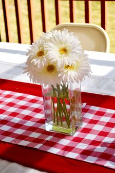 Party Decor Centerpiece from Spark & Chemistry blog- we made this look with minimal materials- I had some left over red fabric we used as a runner and gingham placemats lined on top of that. To finish it off, daisies in a square clear vase! Sweet and simple for a backyard bash!